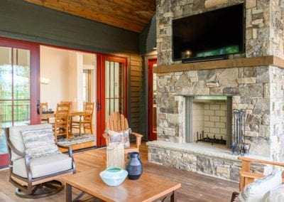 screened deck seating with large stone fireplace and mounted television