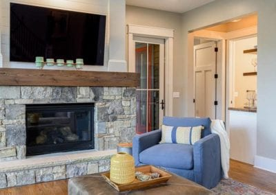 Stone cover fireplace with mounted television and thick wood mantle.